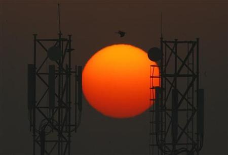 Sun rises over the telecommunication towers in New Delhi December 22, 2007. REUTERS/B Mathur/Files