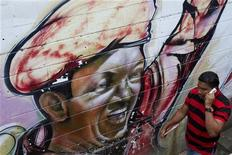 Um homem caminha em frente a um mural representando o presidente venezuelano, Hugo Chávez, em Caracas, Venezuela. 9/01/2013 REUTERS/Carlos Garcia Rawlins