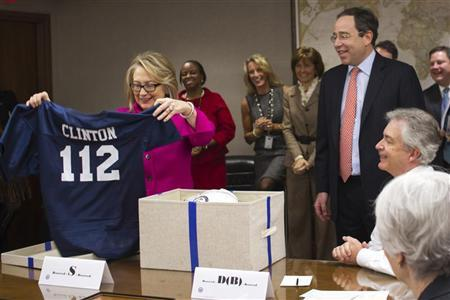 U.S. Secretary of State Hillary Clinton holds up a football jersey with her name on it, presented by Deputy Secretary of State Thomas Nides (2ndR), who joked that ''Washington is a contact sport,'' during a weekly meeting of assistant Secretaries of State, in this handout photograph taken and released by the State Department on January 7, 2013. REUTERS/State Department/Nick Merrill/Handout