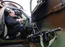"""François Hollande dans un véhicule blindé lors de sa visite au 12e Régiment de cuirassiers d'Olivet, dans le Loiret, à l'occasion de ses voeux aux armées. Le chef de l'Etat a déclaré que l'armée ne serait pas """"la variable d'ajustement"""" du budget national mais devrita participer au redressement des comptes. François Hollande a plaidé pour une loi de programmation militaire réaliste. /Photo prise le 9 janvier 2013/REUTERS/Jacques Brinon/Pool"""