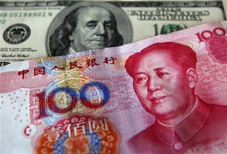 A yuan banknote is displayed next to a U.S. dollar banknote (back) for the photographer at a money changer inside the Taoyuan International Airport March 18, 2010. REUTERS/Nicky Loh