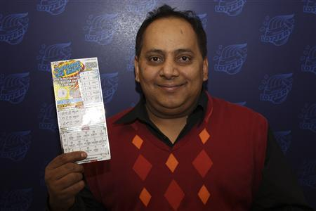 Urooj Khan is pictured holding his winning lottery ticket in this undated handout photo from the Illinois Lottery. Khan died of cyanide poisoning on July 20, 2012, and his death is now a homicide investigation according to media reports, January 9, 2013. REUTERS/Illinois Lottery/Handout
