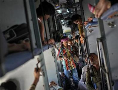 A man sells locks and chains inside a compartment of the Kalka Mail passenger train on the way to Kolkata March 20, 2012. REUTERS/Danish Siddiqui/Files