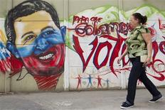 A woman walks past a mural depicting Venezuelan President Hugo Chavez in Caracas January 9, 2013. Chavez's formal swearing-in for a new six-year term scheduled for January 10 can be postponed if he is unable to attend due to his battle to recover from cancer surgery, Venezuela's vice president Nicolas Maduro said. Maduro's comments were the clearest indication yet that the Venezuelan government is preparing to delay the swearing-in while avoiding naming a replacement for Chavez or calling a new election in the South American OPEC nation. REUTERS/Carlos Garcia Rawlins