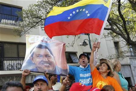 Supporters of Venezuela's President Hugo Chavez hold up a picture of him during the inauguration of the National Assembly in Caracas January 5, 2013. REUTERS/Carlos Garcia Rawlins