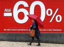El FMI ha identificado recortes del gasto público en Portugal por 4.000 millones de euros, dijo el miércoles el Gobierno, iniciando un debate sobre lo que podría ser un tijeretazo profundamente impopular del estado de bienestar luso que el Ejecutivo califica de insostenible. En la imagen, una mujer camina junto a un anuncio de rebajas en Lisboa, el 9 de enero de 2013. REUTERS/José Manuel Ribeiro