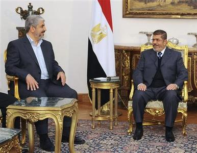 Egyptian President Mohamed Mursi (R) talks with Hamas chief Khaled Meshaal during their meeting in Cairo in this picture provided by the Egyptian Presidency January 9, 2013. REUTERS/Egyptian Presidency/Handout