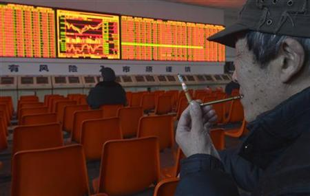 An investor smokes a cigarette through a pipe in front of an electronic board showing stock information at a brokerage house in Taiyuan, Shanxi province December 25, 2012. REUTERS/Stringer/Files
