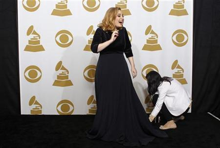 Singer Adele laughs as she is prepared backstage for a photo session with her six Grammy Awards at the 54th annual Grammy Awards in Los Angeles, California February 12, 2012. REUTERS/Lucy Nicholson/fILES