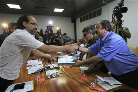 Colombia's FARC rebel group member Andres Paris (R) receives from National University of Colombia professor Marco Romero, proposals on agricultural reforms obtained from a farmers' forum in Colombia, in Havana January 9, 2013. REUTERS/Enrique De La Osa