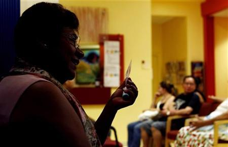 Paula, who asked to have her last name withheld, holds a membership card to the DC Health Care Alliance, as she is interviewed near the waiting room of the La Clinica Del Pueblo community health clinic in Washington, August 2, 2012. REUTERS/Gary Cameron/Files