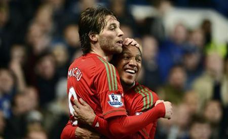 Swansea City's Michu (L) celebrates with team mate Jonathan de Guzman after scoring against Chelsea during their English League Cup semi-final soccer match at Stamford Bridge in London January 9, 2013. REUTERS/Dylan Martinez