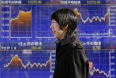 Un passante accanto ai monitor con i grafici delle azioni quotate alla Borsa di Tokyo, 27 dicembre 2012. REUTERS/Yuriko Nakao