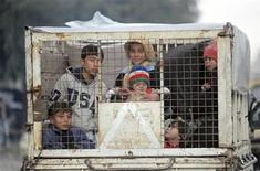 Children sit in a small truck in Aleppo city January 9, 2013. REUTERS/Muzaffar Salman