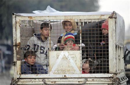 Children sit in a small truck in Aleppo city January 9, 2013. REUTERS/Muzaffar Salman