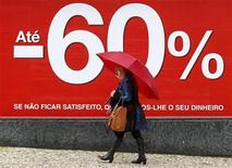 A woman walks past a shop announcing discounts up to 60 percent on a street in Lisbon January 9, 2013. REUTERS/Jose Manuel Ribeiro