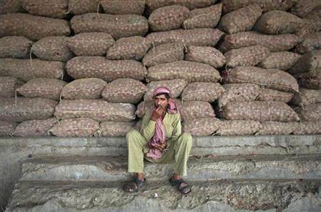 A labourer sits in front of stacked sacks of onions at a wholesale vegetable market on the outskirts of Jammu November 14, 2012. REUTERS/Mukesh Gupta/Files