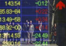 El Índice Nikkei subió el jueves en un mercado de alta participación ante una renovada debilidad en el yen que fortaleció a las acciones de los exportadores, mientras que los buenos datos de comercio de China mejoraron la tónica inversora. En la imagen, varias personas se reflejan en un monitor electrónico con los índices bursátiles en Tokio, el 27 de diciembre de 2012. REUTERS/Yuriko Nakao