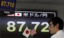 El yen estaba a la defensiva en Asia y cerca del mínimo de dos años y medio por las expectativas de que el Banco de Japón adopte nuevas medidas para potenciar la economía, mientras que el dólar australiano se fortaleció por unas cifras de comercio chinas que superaron lo previsto. En la imagen, un empleado de una compañía de cambio junto a un tablero electrónico que muestra el tipo del cambio del yen frente al dólar, en Tokio, el 4 de enero de 2013. REUTERS/Toru Hanai