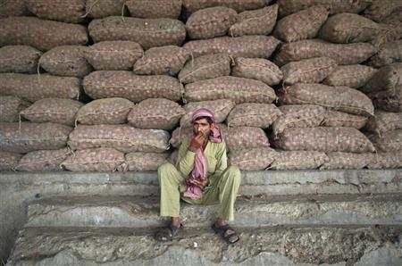 A labourer sits in front of stacked sacks of onions at a wholesale vegetable market on the outskirts of Jammu November 14, 2012. REUTERS/Mukesh Gupta