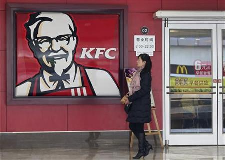 A woman walks past a KFC restaurant as a logo of McDonald is reflected on a door window, in Wuhan, Hubei province, December 18, 2012. REUTERS/Stringer/Files