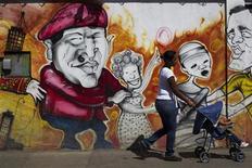 El Gobierno venezolano celebrará el jueves una toma de posesión simbólica para marcar el comienzo del tercer mandato del presidente Hugo Chávez, a quien no se ha visto en público desde que fuera operado de urgencia en Cuba hace un mes. En la imagen, una mujer pasa con un carrito de bebé frente a una pintada de Chávez en Caracas, el 9 de enero de 2013. REUTERS/Carlos Garcia Rawlins