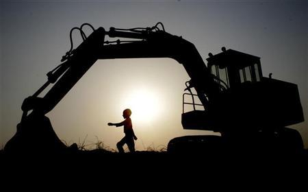 A boy walks under an excavator against the setting sun in Chandigarh September 8, 2007. REUTERS/Ajay Verma/Files