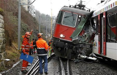 Swiss firemen stand beside a demolished RE 440 train after a train crash in the northern Swiss town of Neuhausen am Rheinfall January 10, 2013. REUTERS/Arnd Wiegmann