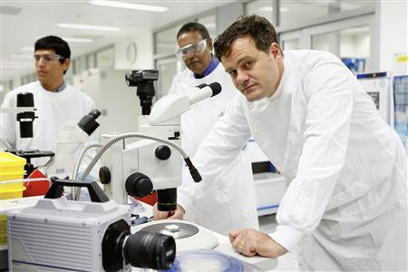 Biomedical engineer Mark Kendall (R) poses beside a stereo microscope in a laboratory in Brisbane in this handout photograph taken in 2012. REUTERS/Rolex Awards/Julian Kingma/Handout