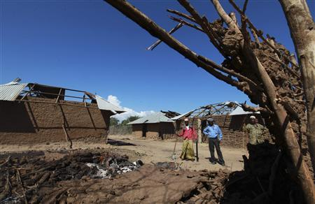 Residents look at a house that was destroyed when their village was attacked in Nduru village at Tana Delta region of the Kenyan Coast, January 9, 2013. REUTERS/Joseph Okanga