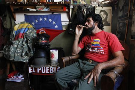 Humberto Lopez, known as ''El Che'', smokes a cigar at his house in Caracas January 8, 2013. A flamboyant look-a-like of Latin American revolutionary Ernesto ''Che'' Guevara has for years been a familiar sight on the streets of Venezuela whipping up support for his other socialist hero, President Hugo Chavez. Yet 54-year-old Lopez cuts a more subdued figure these days as he waits and prays for better news from Cuba where Chavez is battling to recover from cancer surgery. Picture taken January 8, 2013. REUTERS/Carlos Garcia Rawlins