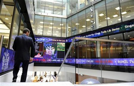 A man walks down a staircase near a stock ticker in the lobby of the London Stock Exchange, in central London September 22, 2011. REUTERS/Paul Hackett