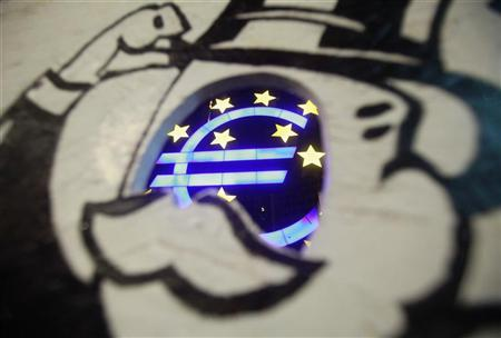 A sculpture showing the Euro currency sign is seen through a photo board installed by Occupy protestors in front of the European Central Bank (ECB) headquarters in Frankfurt June 29, 2012. REUTERS/Alex Domansk/Files