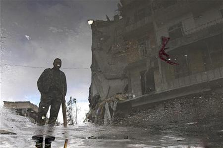 A Free Syrian Army fighter is reflected in a puddle of water as he stands near a damaged building in Aleppo January 6, 2013. Picture rotated 180 degrees. REUTERS/Muzaffar Salman