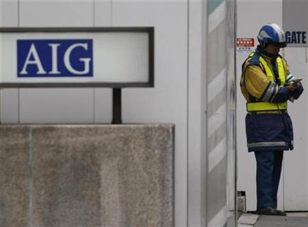 A construction worker stands near an AIG logo in Tokyo March 3, 2009. REUTERS/Issei Kato (JAPAN)