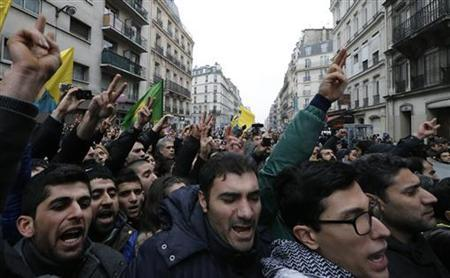 Members of the Kurdish community shout slogans as they gather in front of the entrance of the Information Centre of Kurdistan in Paris, where three Kurdish women were found shot dead, January 10, 2013. REUTERS/Christian Hartmann (FRANCE - Tags: POLITICS CRIME LAW CIVIL UNREST)