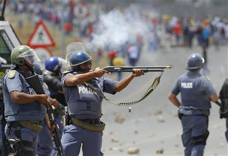 Police fire on demonstrators during a strike by farm workers at De Doorns on the N1 highway, linking Cape Town and Johannesburg, January 9, 2013. Police fired rubber bullets and stun grenades at hundreds of striking farm workers who blocked a highway in the grape-growing Western Cape on Wednesday, the first clashes of a year likely to be marked by fractious labour relations. REUTERS/Mike Hutchings