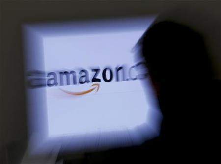 A zoomed illustration image of a man looking at a computer monitor showing the logo of Amazon is seen in Vienna November 26, 2012. REUTERS/Leonhard Foeger/Files