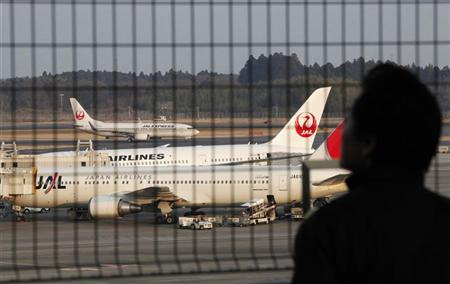 A man looks at Japan Airlines' airplanes including Boeing Co's 787 plane (C) at New Tokyo international airport in Narita, east of Tokyo Janauary 9, 2013. REUTERS/Shohei Miyano