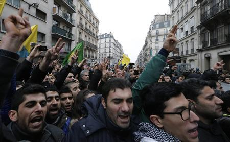 Members of the Kurdish community shout slogans as they gather in front of the entrance of the Information Centre of Kurdistan in Paris, where three Kurdish women were found shot dead, January 10, 2013. REUTERS/Christian Hartmann