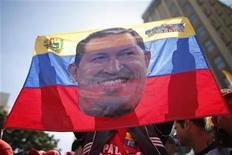 Un partidario del presidente de Venezuela, Hugo Chávez, sostiene una bandera con su imagen en las afueras del palacio de Gobierno en Caracas, ene 10 2013. Los venezolanos celebraban el jueves el inicio de un nuevo mandato presidencial Hugo Chávez, un festejo marcado por la ausencia del líder socialista que lleva un mes hospitalizado en Cuba tras una cirugía por el cáncer que padece y que podría alejarlo del mando de la potencia petrolera. REUTERS/Jorge Silva