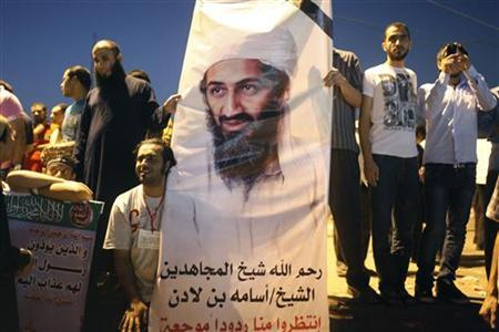 Demonstrators carry a poster of Osama Bin Laden during a protest in Tahrir Square September 14, 2012. The poster reads: ''May God have mercy on the soul of Sheikh Osama Bin Laden. Wait for more hurtful reactions from us.'' REUTERS/Asmaa Waguih/Files
