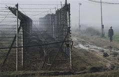 An Indian Border Security Force (BSF) soldier patrols near the fenced border with Pakistan amid fog in Suchetgarh, southwest of Jammu January 10, 2013. REUTERS/Mukesh Gupta