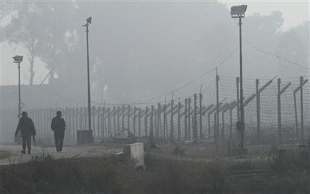 Indian Border Security Force (BSF) soldiers patrol near the fenced border with Pakistan amid fog in Suchetgarh, southwest of Jammu January 10, 2013. REUTERS/Mukesh Gupta