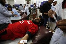 An injured rescue worker receives treatment in a hospital after the second bomb blast in Quetta January 10, 2013. REUTERS/Naseer Ahmed