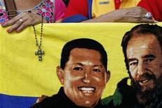 Apoiador do presidente venezuelano, Hugo Chávez, segura crucifixo perto da imagem de Chávez e do ex-líder Fidel Castro (D), em Caracas. Chávez segue acamado em Cuba enquanto seus partidários se preparam para uma grande demonstração de apoio no dia em que ele deveria tomar posse para um novo mandato de seis anos. 05/01/2013 REUTERS/Carlos Garcia Rawlins