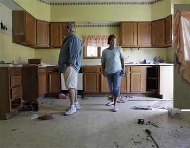 Joseph Keller (L), and his wife Jennifer look through their abandoned house in Columbus, Ohio, September 30, 2012. Five years ago, the Kellers received an eviction notice from JP Morgan Chase ordering them to vacate their home because the bank was putting it up for sale. It turned out that the bank never followed through with the foreclosure sale leaving the Kellers responsible for back taxes and code violations on a house that had since been stripped to its studs and rendered worthless. Picture taken September 30, 2012. REUTERS-Jay LaPrete