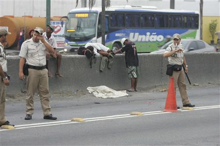 The body of a boy lies covered on a road as police officers control traffic at the Brasil Avenue during an operation by Rio de Janeiro's Social Action Secretariat to bring crack addicts to shelters for rehabilitation, in Rio de Janeiro January 10, 2013 in this picture provided by Ag.O Dia. REUTERS/Osvaldo Praddo /Ag.O Dia