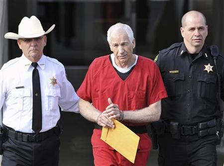 Jerry Sandusky (C) leaves the Centre County Courthouse after his sentencing in his child sex abuse case in Bellefonte, Pennsylvania October 9, 2012. REUTERS/Pat Little