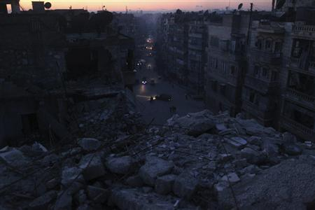 Cars drive past damaged houses during sunset in Aleppo city January 10, 2013. REUTERS/Muzaffar Salman